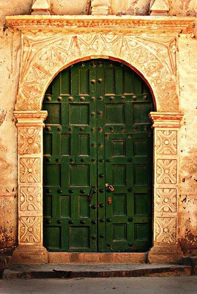 Симметричная дверь с узорами как на самой двери, так и на арке здания.